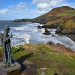 Picture of a statue of a saint overlooking a beach and cliffs