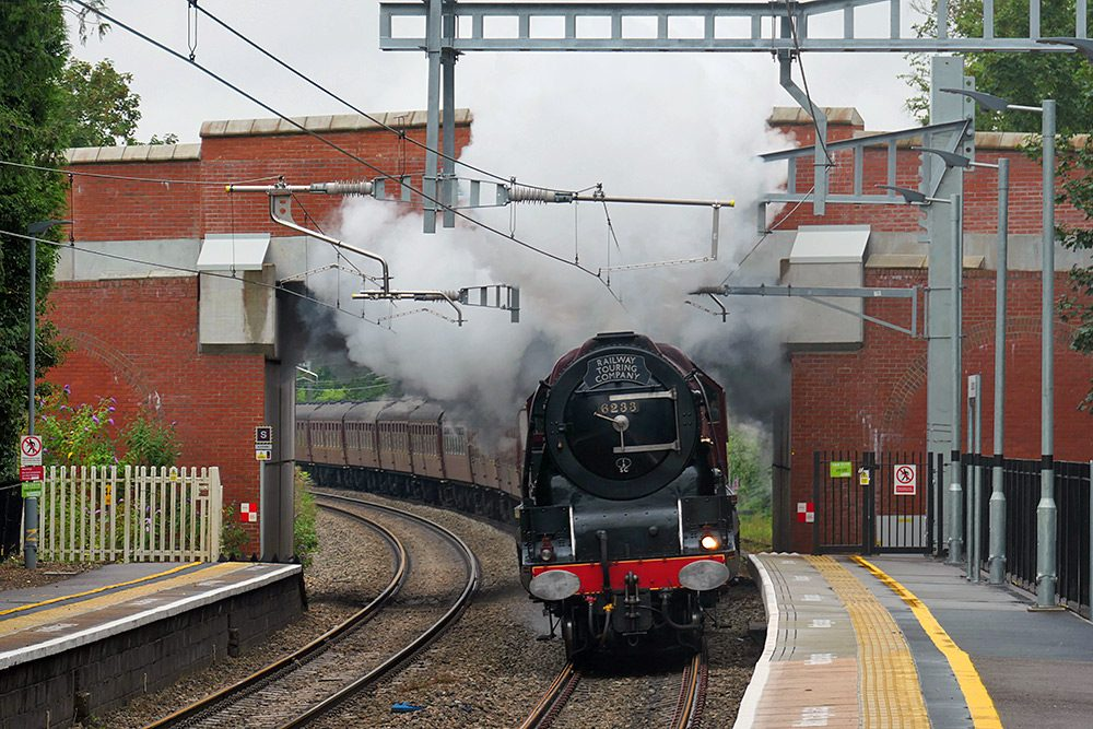 Picture of a steam train passing under a road bridge