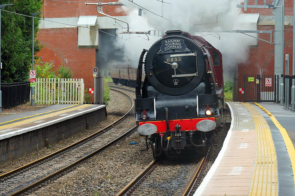 Picture of a steam train passing a rural train station