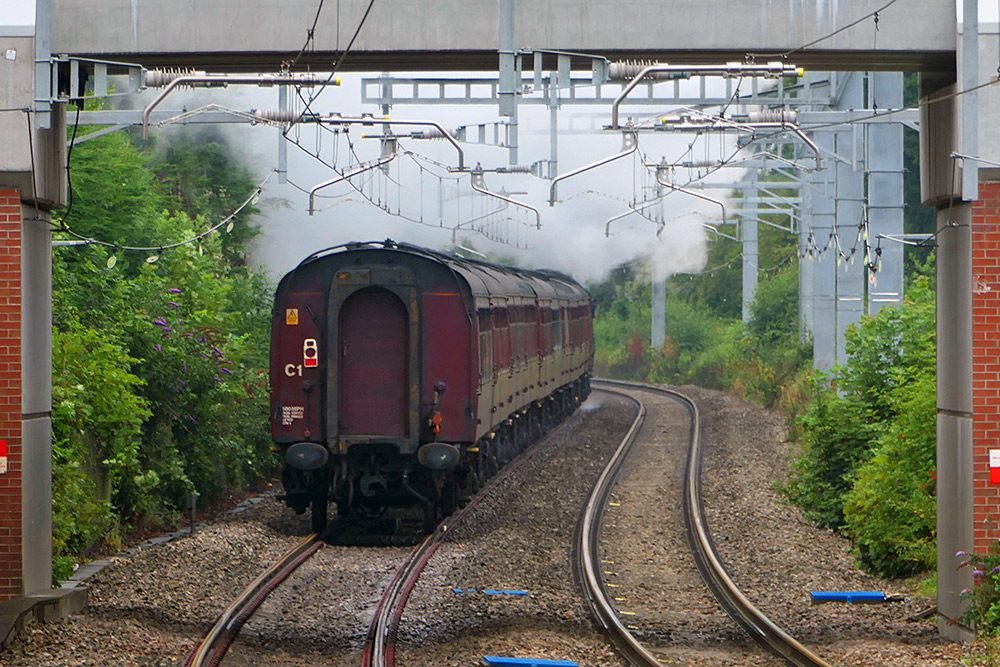 Picture of a steam train from behind, steaming away into the distance
