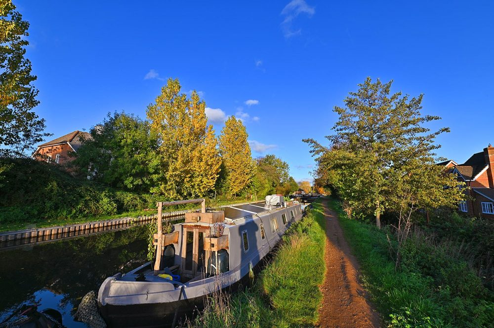 Picture of a canal boat moored along a canal in the autumn sunshine, trees in their autumn colour in the background