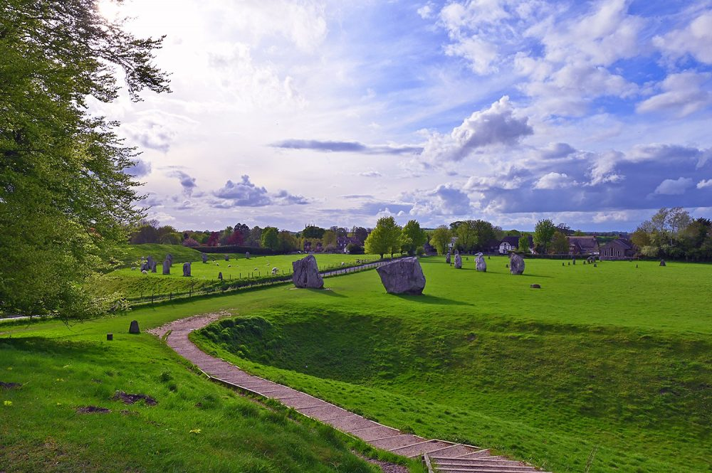 Picture of a stone circle seen from an embankment on a May evening with sunny intervals